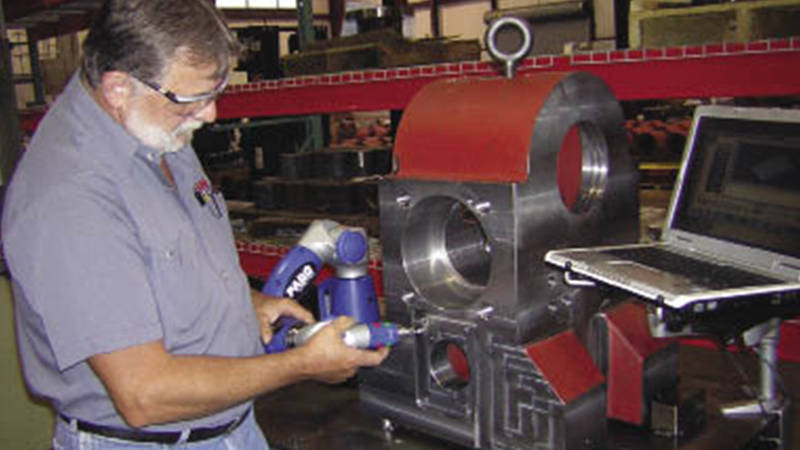 A worker using a FARO 3D laser scanner for machined parts measurement