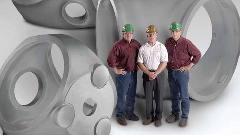 Three workers at ATI Casting standing with three large wind turbine hubs