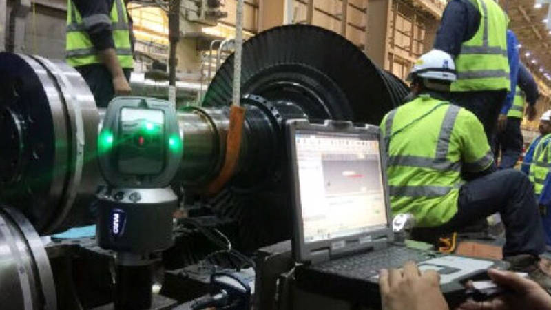 Workers around a large machine referencing FARO 3D scanning data on a laptop