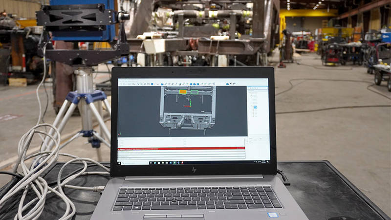 A parts assembly scan displayed on a laptop near assembly inspection equipment