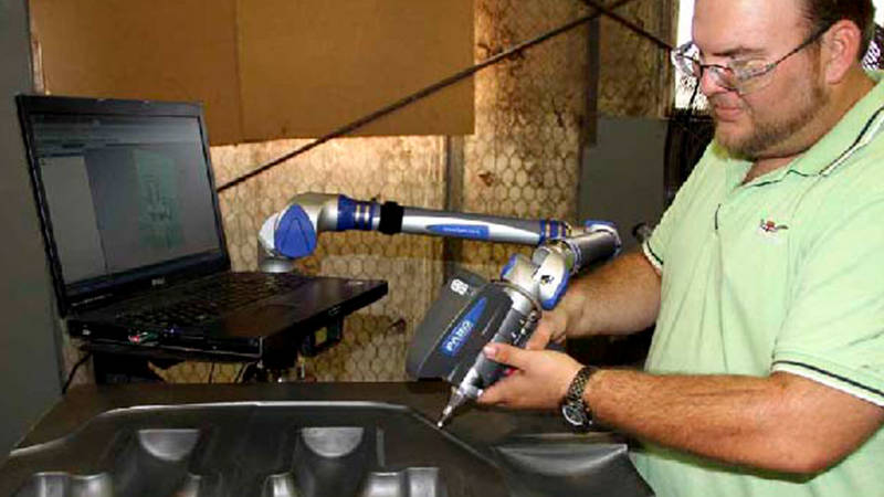 A worker uses a FARO 3D laser scanner to check a die made with forging equipment
