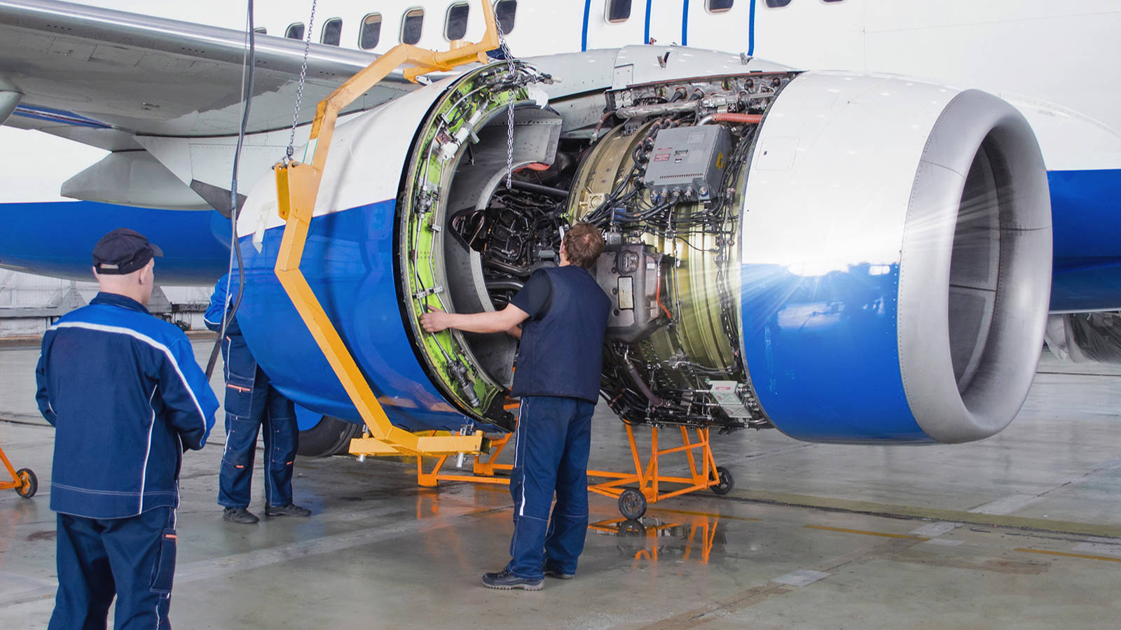 Two workers replacing an airplane engine with a device that required careful tool building measurement