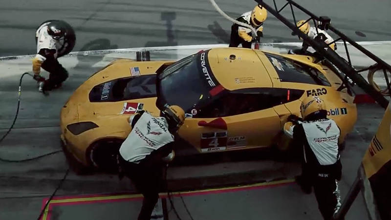 Five members of a pit crew checking a yellow Corvette