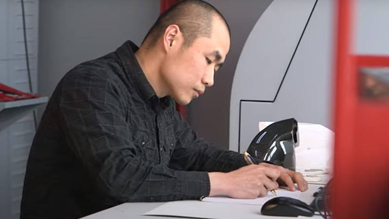 An automotive engineering professional at a desk, sketching a new Ferrari engine bay design