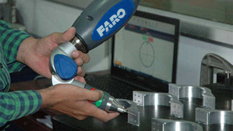 A close-up of a Unitech worker's hands using the Gage FaroArm for 3D scanning of missile components