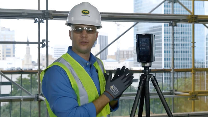 A construction worker using BIM technology and 3D scanning on a job site