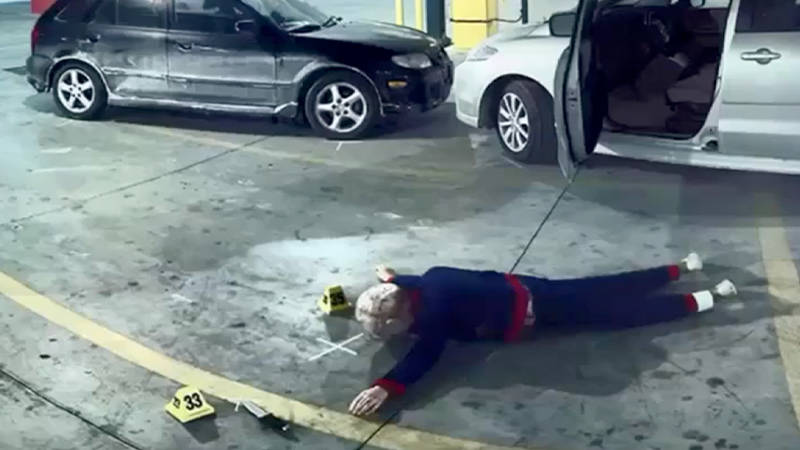 A body lying face down on the ground near two vehicles with evidence marked for forensic reconstruction