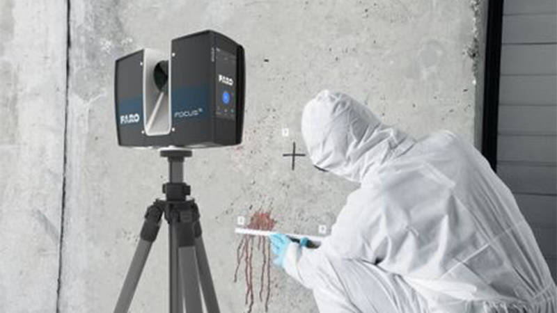A forensic tech expert in safety gear studying a stain on a wall for 3D scanning