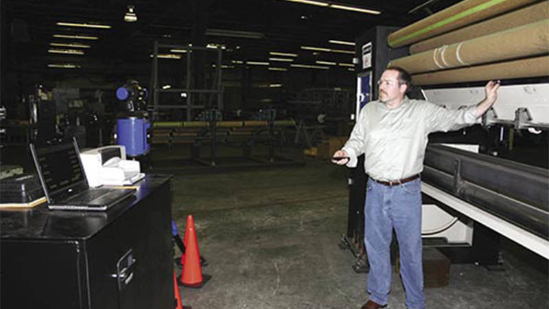 A worker at Tuftco Corporation adjusting a large carpet tufting machine