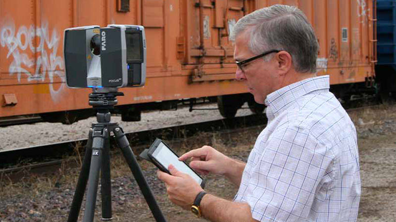 A man using a mobile device and FARO 3D scanning device near a train