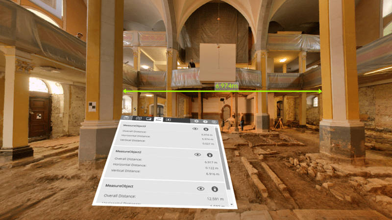 A virtual-reality view of a large room showing measured distance between two columns