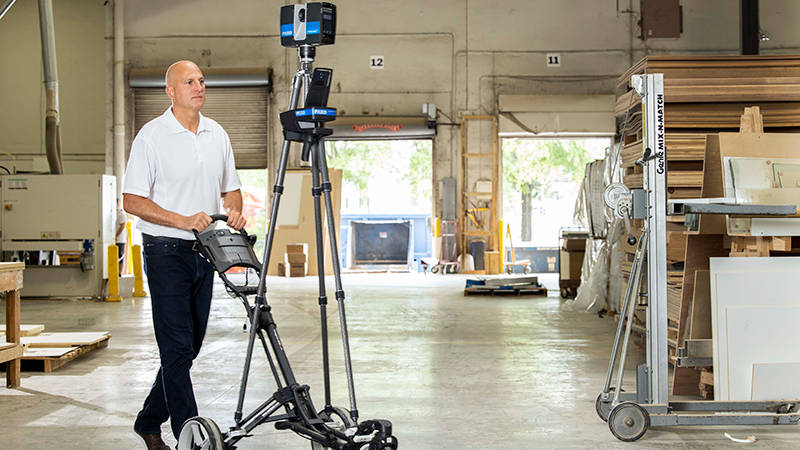 A worker moving a 3D laser scanner across a warehouse