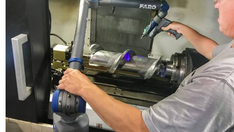A worker using a FARO non-contact measuring machine to capture 3D measurements