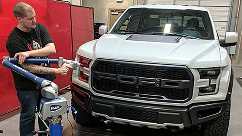A worker uses a FARO 3D laser scanner to capture measurements of a vehicle part for aftermarket production