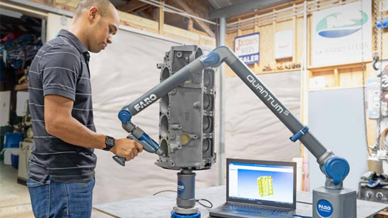 A worker using a FARO device and reverse engineering software to capture precision measurements of a part
