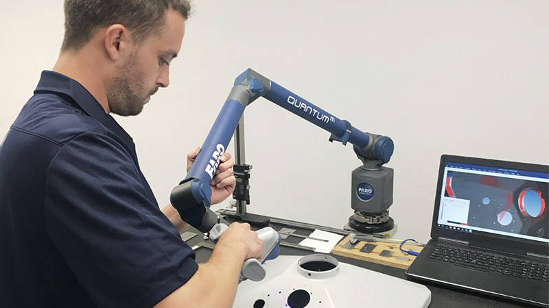 A worker using a FARO ScanArm to inspect a part for a plastic products manufacturer