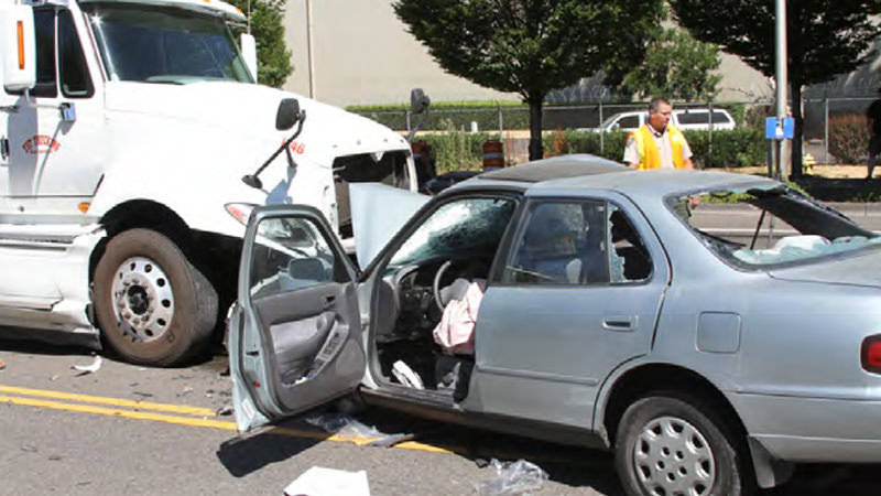 A crash scene involving a car and a semitruck
