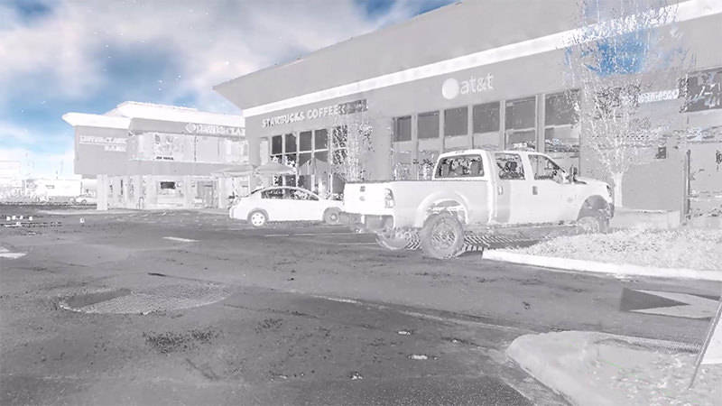 A virtual-reality image of two vehicles parked by stores, captured with 3D scanning