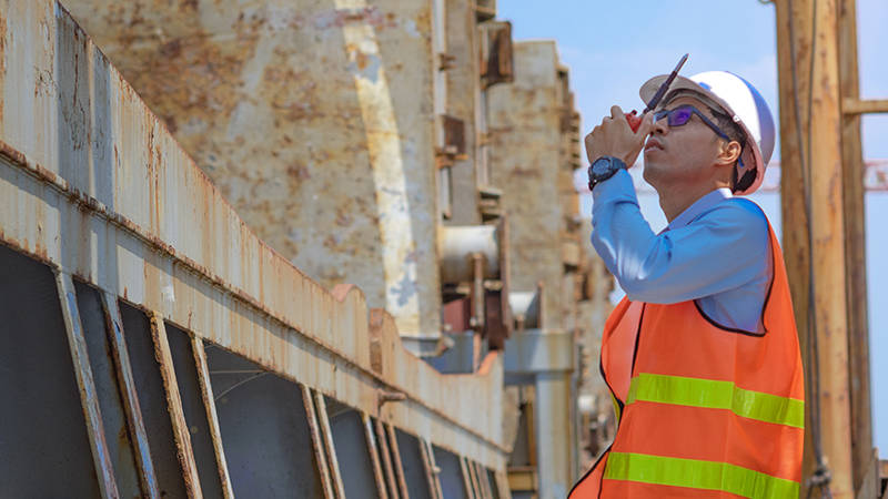 A director of quality speaking into a walkie-talkie during quality control inspection