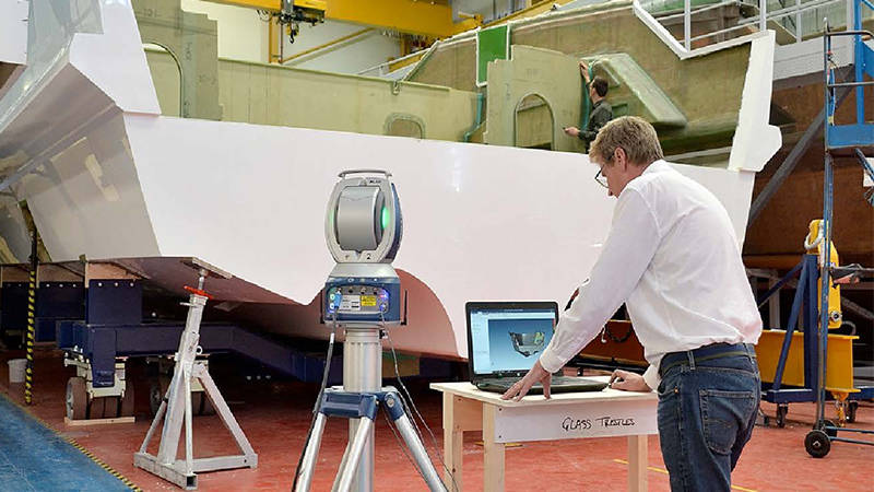 A worker reviewing a 3D scan of a manufactured yacht component for quality control